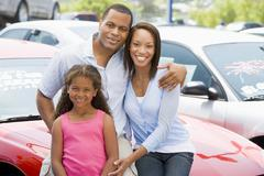 Mother and father with young daughter shopping for a new car Stock Photos