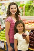 Woman and daughter shopping for apples at a grocery store Stock Photos