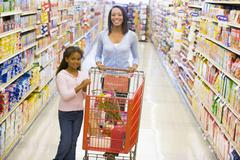 Mother and young daughter shopping at a grocery store - stock photo