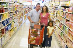 Mother and father with young daughter shopping at the grocery store. Stock Photos