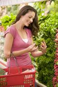 Woman shopping for herbs at a grocery store - stock photo