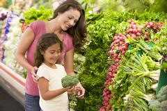 Mother and daughter shopping for broccoli at a grocery store Stock Photos