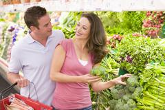 Young couple shopping for broccoli at a grocery store Stock Photos