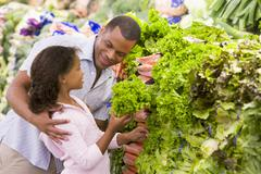 Father and daughter shopping for lettuce at a grocery store - stock photo