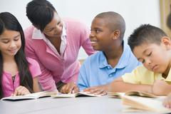 Students in class reading with teacher helping (selective focus) - stock photo