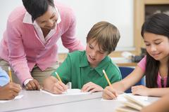 Students in class writing with teacher helping Stock Photos