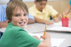 Students in class writing (selective focus) - stock photo
