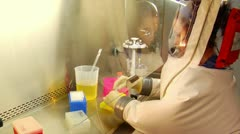 Stock Video Footage of scientist in bubble suit uses pipette to transfer samples