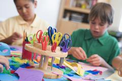 Students in art class with supplies in foreground (selective focus) - stock photo