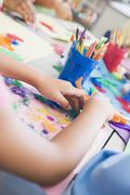 Students in art class focusing on hands (selective focus) - stock photo