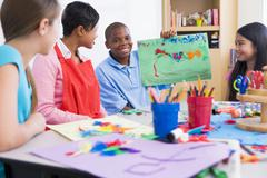 Student showing teacher and classmates his artwork (selective focus) - stock photo