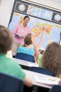 Students in geography class volunteering for teacher (selective focus) - stock photo