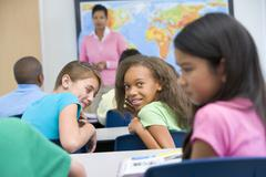 Students in class bullying student with teacher in background (selective focus) Stock Photos