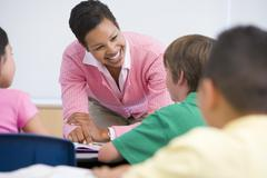 Teacher helping student in class (selective focus) - stock photo