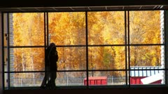 people walk by large windows with fall leaves - stock footage