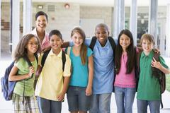Six students standing outside school with teacher - stock photo
