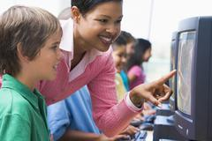 Teacher helping student at computer terminal with students in background (depth - stock photo