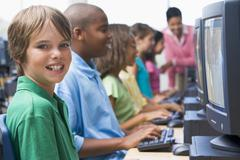 Six children at computer terminals with teacher in background (depth of Stock Photos