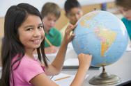 Stock Photo of Student in class pointing at a globe (selective focus)