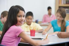 Students in class taking notes with teacher in background (selective focus) - stock photo