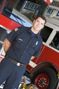 Fireman standing in front of fire engines - stock photo