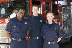 Three firefighters standing in front of fire engine Stock Photos