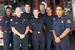 Six firefighters standing in front of fire engine with captain (depth of field) - stock photo