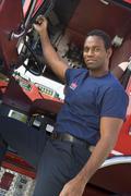 Fireman leaning in door of fire engine - stock photo