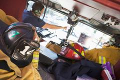 Two firefighters driving a fire engine with gear in the back (selective focus) - stock photo