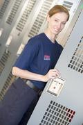 Firewoman holding her locker door open in fire station locker room (depth of - stock photo