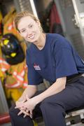 Firewoman sitting on bench in fire station locker room Stock Photos