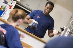 Three firefighters in break room with one getting coffee (selective focus) Stock Photos