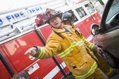 Fireman pointing at something with another fireman using the jaws of life on a - stock photo