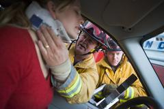 Fireman helping woman with neck brace while another fireman uses the jaws of - stock photo