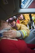 Fireman helping woman with neck brace while another fireman uses the jaws of Stock Photos
