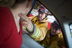 Fireman taking woman's pulse while another fireman watches (selective focus) - stock photo