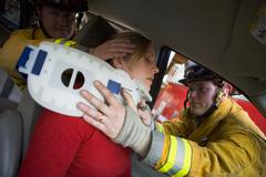 Two firemen helping woman with neck brace - stock photo