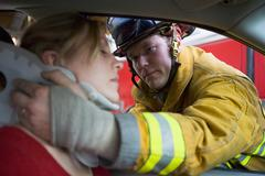 Fireman helping woman with neck brace (selective focus) - stock photo