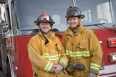 Two firemen standing in front of fire engine Stock Photos