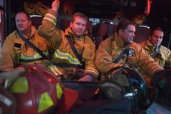 Four firemen in fire engine with gear Stock Photos