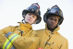 Two firefighters standing outdoors wearing helmets Stock Photos