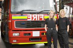 Two firefighters standing in front of fire engine - stock photo