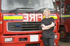 Firewoman standing in front of fire engine - stock photo