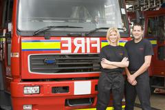 Two firefighters standing in front of fire engine Stock Photos