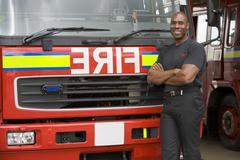 Fireman standing in front of fire engine Stock Photos