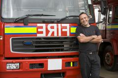 Fireman standing in front of fire engine - stock photo