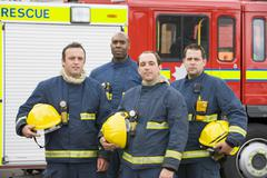 Four firefighters standing by fire engine Stock Photos