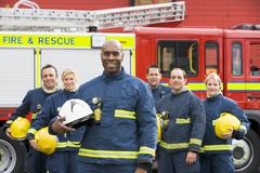 Six firefighters standing by fire engine - stock photo