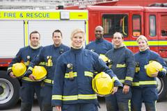 Six firefighters standing by fire engine Stock Photos
