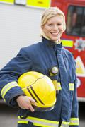 Firewoman standing by fire engine - stock photo